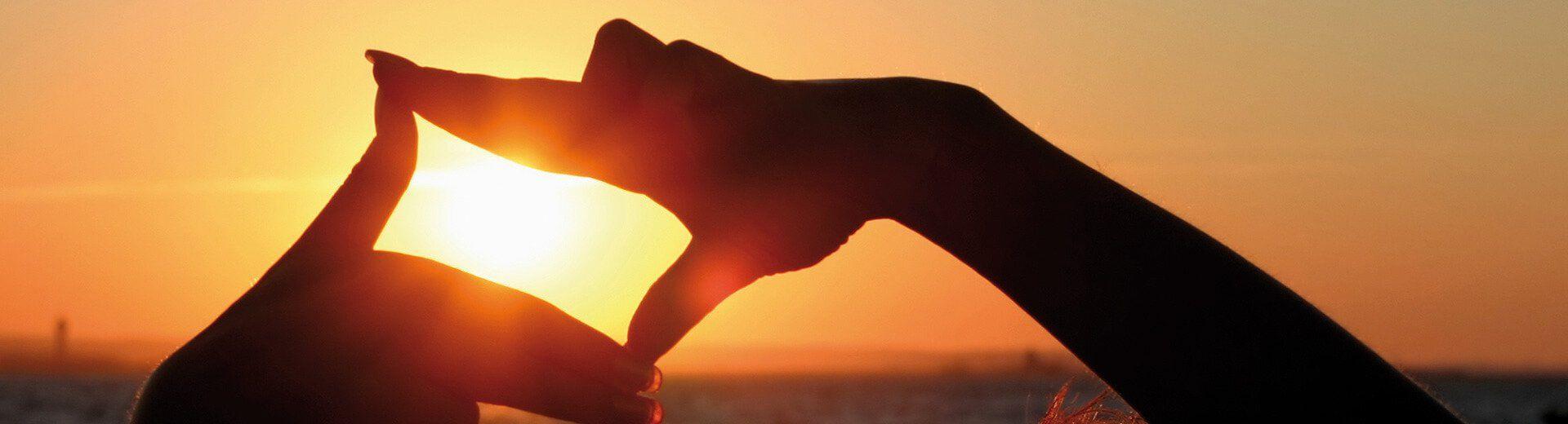 Full HD hero image sunset hands framing sun